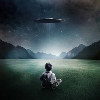 Boy Sitting On Ground Looking At UFO In The Night Sky