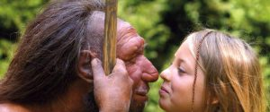 Male neanderthal and human woman touching noses.